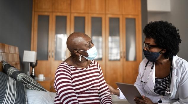 Doctor hablando con el paciente en máscara
